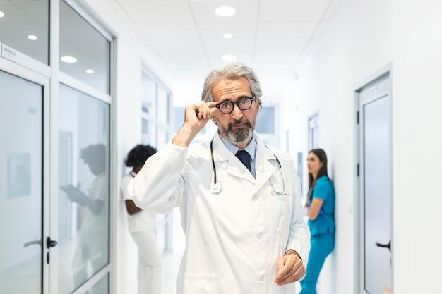 病院の廊下で彼の眼鏡を保持している自信を持って成熟した医師の肖像画。