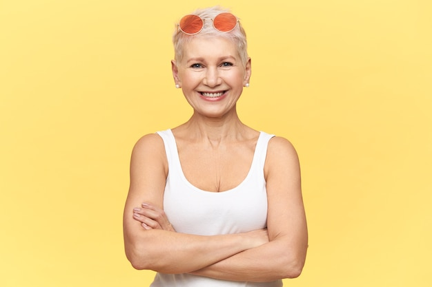幸せな笑顔でカメラを見て、彼女の胸に腕を組んで、白いタンクトップとサングラスを身に着けている暑い晴れた天気を楽しんで日焼けしたスポーティな体を持つ自信を持って中年の女性の肖像画