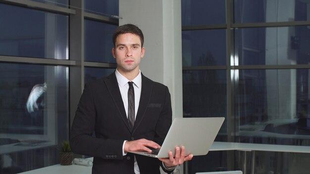 手にノートパソコンと自信を持って近代的なビジネスマンの肖像画