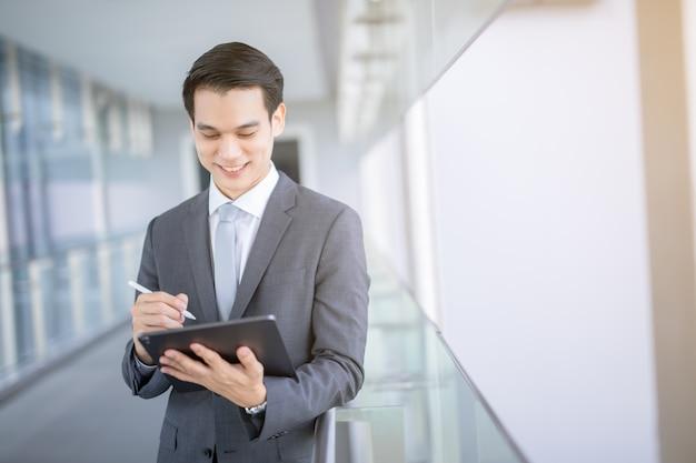 自信を持って現代の若いアジア系のビジネスマンの肖像画は、デジタルタブレットを持っている黒いスーツの手を着用します。