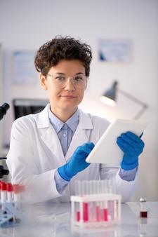 実験室で血液サンプルとテーブルに座って、タブレットを使用して白衣とゴーグルで自信を持って製薬研究者の肖像画