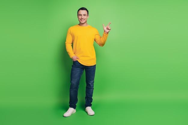 緑の背景に自信を持ってプロモーターの男の手のポケット直接指の空きスペースの肖像画