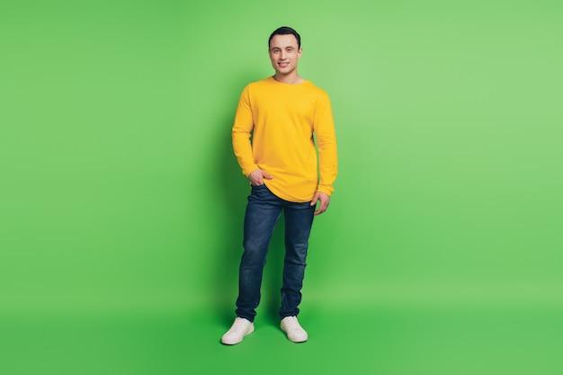 緑の背景にポーズをとって自信を持って信頼できる男の手のポケットの肖像画