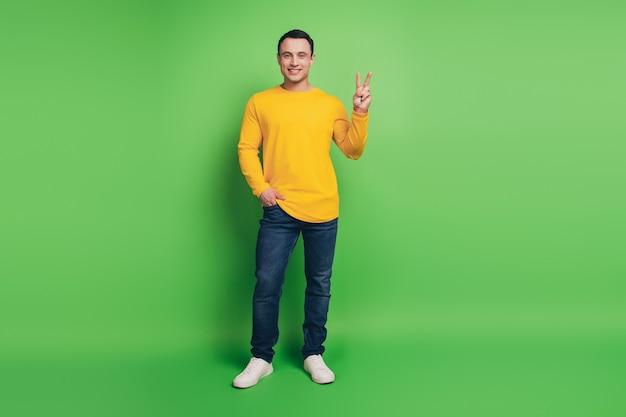 緑の背景に自信を持って信頼できる男の手のポケットショーvサインの肖像画