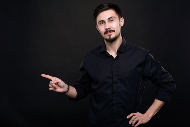 Портрет уверенного менеджера по продажам с усами и бородой, указывая пальцем в сторону, рекомендуя продукт