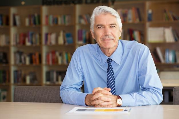 Портрет уверен старший бизнесмен в офисе
