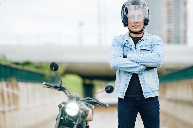 腕を組んで屋外に立っているオートバイのヘルメットに自信を持って真面目なアジア人男性の肖像画
