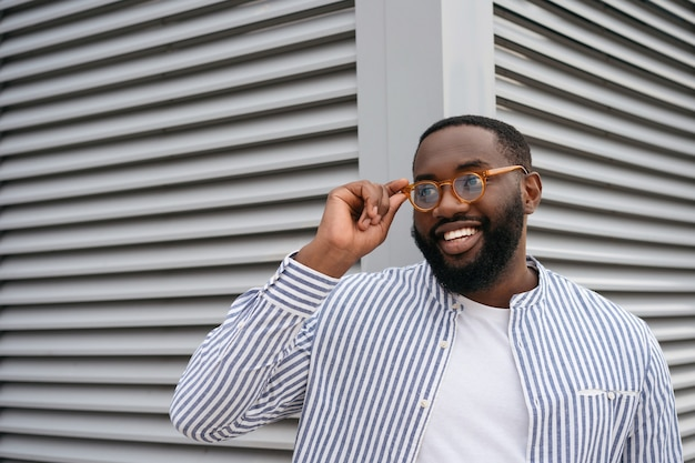 Портрет уверенно улыбающегося африканца в стильных очках на сером фоне