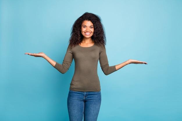 自信を持って成功したムラートの女の子のプロモーターの肖像画は、手を差し伸べるオブジェクトの広告をお勧めしますプロモーション販売は、青い色の上に分離されたスタイリッシュな緑の服のデニムジーンズを着用します