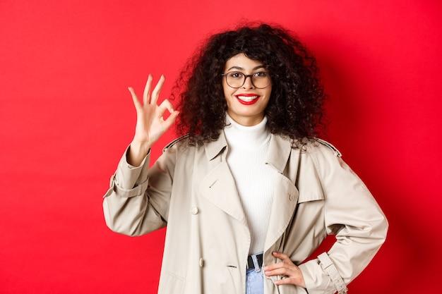 Портрет уверенной в себе модной женщины в очках и плаще, демонстрирующей нормальный жест, чтобы одобрить или согласиться с вами, сказать «да», стоя на красном фоне.