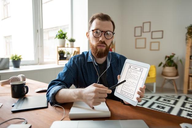 Портрет уверенного ui-дизайнера в очках, указывающего на экран планшета и представляющего дизайн интерфейса во время разговора через приложение для видеоконференцсвязи
