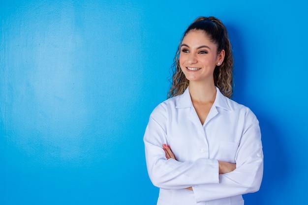 歯を見せる笑顔に自信のある肖像画は、白いフォーマルウェアを身に着けている経験豊富な賢いインテリジェントな医師の資格を持っています