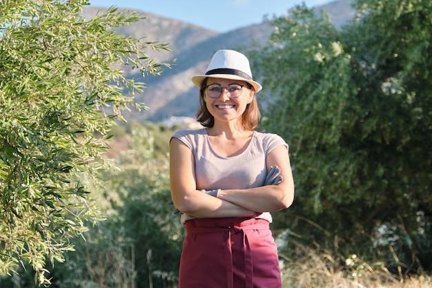 自信を持って女性のオリーブファームの所有者、山の背景のオリーブの木の肖像画