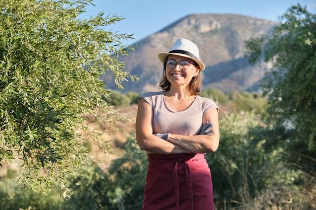 自信を持って女性のオリーブファームの所有者、山の背景オリーブの木の肖像画