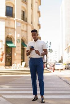 カジュアルな服を着て、携帯電話を使用して自信を持って若いアフリカの実業家の肖像画