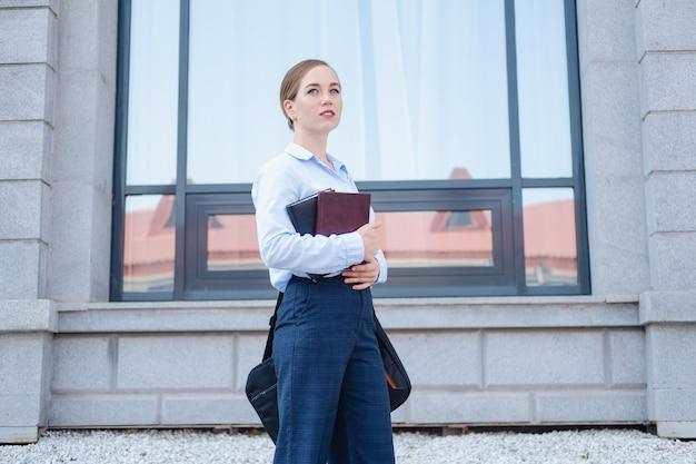 자신감 있는 젊은 비즈니스 여성의 초상화, 노트북과 노트북, 책으로 도시를 걸어보세요. 일하러 가다. 고품질 사진