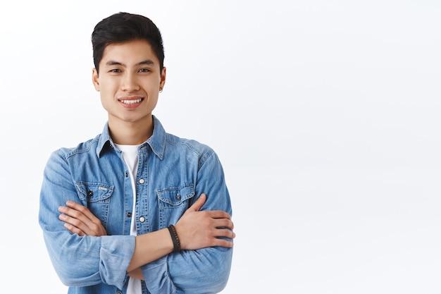 자신감 있는 젊은 힙스터 남성의 초상화, 데님 재킷을 입은 아시아 남성이 캠퍼스에서 친구들과 이야기하고, 가슴에 손을 얹고 캐주얼한 포즈를 취하고, 기쁘게 웃고, 언어 과정을 추천하고, 흰 벽