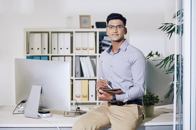 手にタブレットコンピューターを持ってオフィスの机の端に座って、カメラを見ている自信を持って若いインドの起業家の肖像画