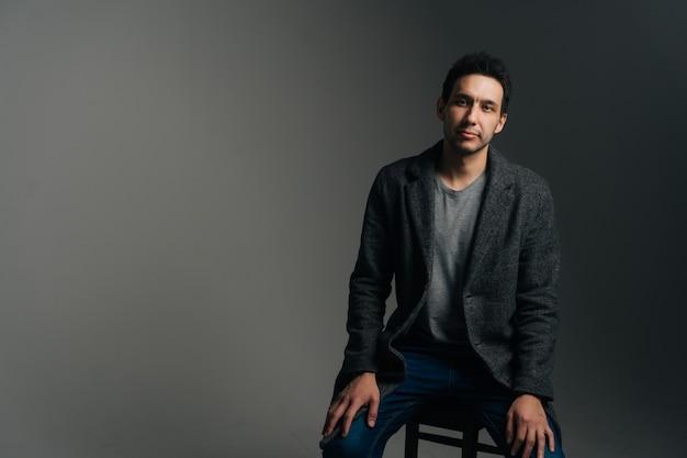 Портрет уверенно молодого человека в стильном длинном пальто, сидящего в кресле на черном изолированном фоне, глядя на камеру. студия выстрел из серьезных кавказских мужчин позирует на темной стене.