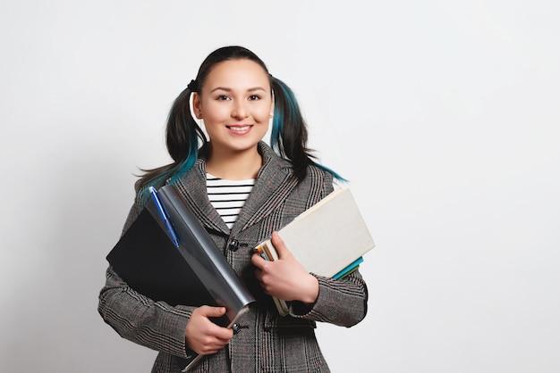 Портрет уверенно молодой студентки, держащей книги и папки