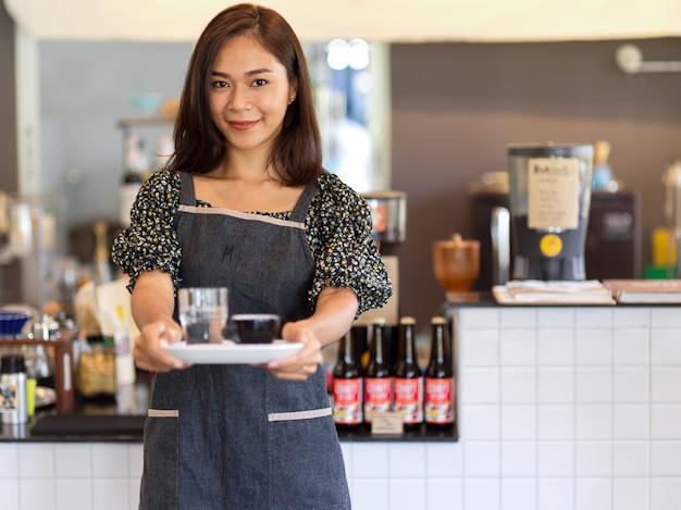 Портрет уверенной молодой женщины-бариста, держащей кофе с подносом перед прилавком в кафе