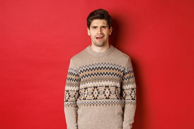 크리스마스 스웨터를 입은 혼란스러운 성인 남자의 초상화, 새해 연휴 동안 실망한 채, 빨간색 배경 위에 서서 뭔가를 이해하지 못합니다.