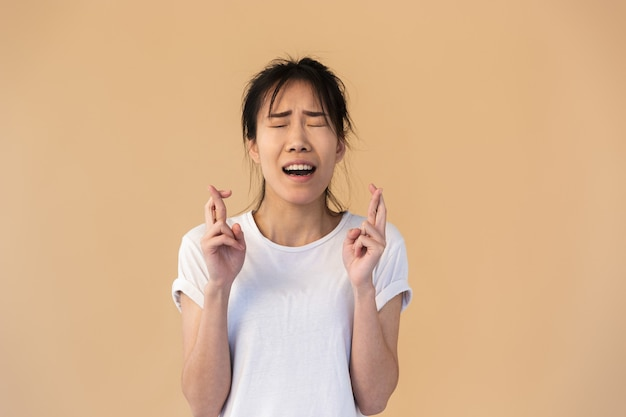神を懇願する基本的なtシャツを着ている混乱したアジアの女性の肖像画は、スタジオでベージュの壁を越えて孤立した指を交差させてください