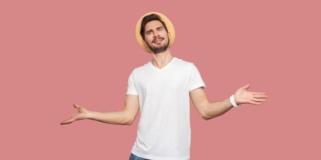 Портрет сбитого с толку бородатого молодого человека в белой рубашке с шляпой, стоящего с поднятыми руками и смотрящего в камеру с серьезным лицом. крытая студия выстрел, изолированные на розовом фоне copyspace.