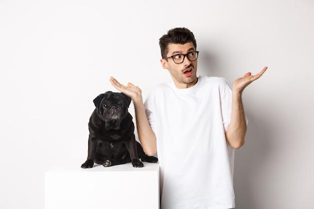 Портрет сбитого с толку хозяина собаки-хипстера, пожимая плечами, стоя возле милого черного мопса, белый фон