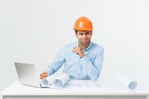 Портрет сбитого с толку мужчины-дизайнера или архитектора, чувствует стресс, нервничает, держит руку за голову, смотрит в план. измученный человек создает стройку в одиночку, у него какие-то неприятности.