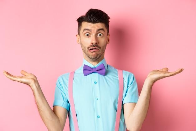 Портрет растерянной мужской модели в галстуке-бабочке и забавной рубашке, пожимающей плечами и выглядящей невежественной, ничего не знающей, стоящей на розовом.