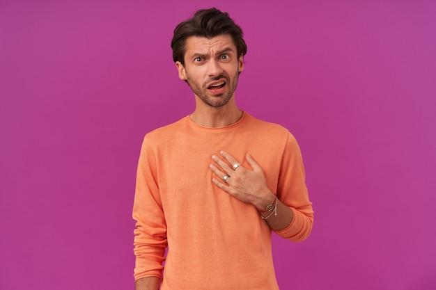 ブルネットの髪と剛毛で混乱した男性の肖像画。袖をまくり上げたオレンジ色のセーターを着ています。自分を指さして尋ねる