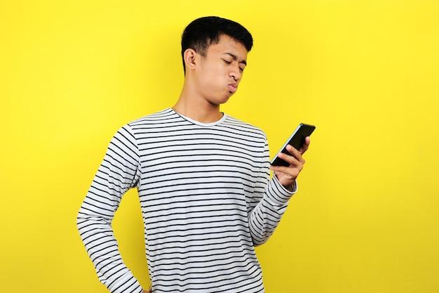 노란색 배경에 격리된 스마트폰을 보고 있는 혼란스러운 남자의 초상화