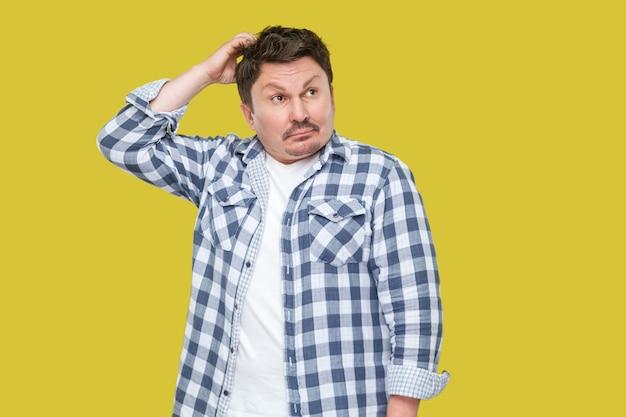 Портрет смущенного или вдумчивого красивого бизнесмена средних лет в случайной клетчатой рубашке, стоящего, касаясь его головы и думающего, что делать. крытая студия выстрел, изолированные на желтом фоне.