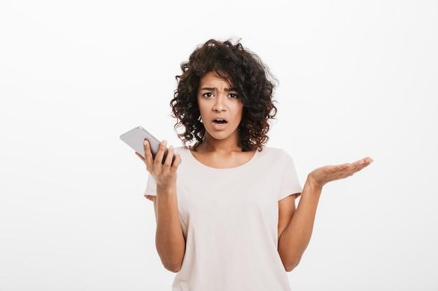 白い壁に分離された携帯電話を保持していると誤解を表現するtシャツを着てアフロのヘアスタイルで困惑した困惑した女性の肖像画