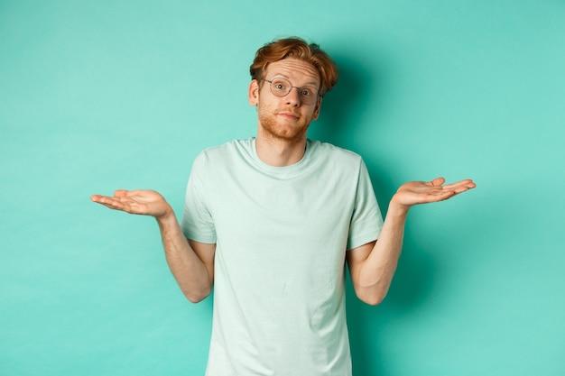 T- 셔츠와 안경에 혼란스러운 빨간 머리 남자의 초상화는 아무것도 모르고, 어깨를 으쓱하고, 청록색 배경에 서서 카메라를 멍하니 바라보고 있습니다.