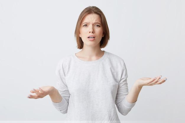 Портрет растерянной расстроенной молодой женщины в лонгсливе выглядит озадаченным