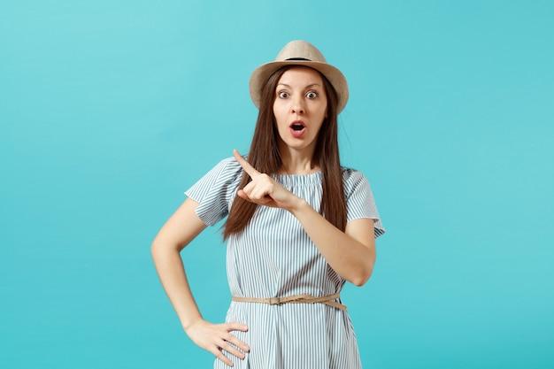 ドレス、青い背景で隔離のコピースペースに人差し指を指すわらの夏の帽子を身に着けている混乱した若いエレガントな女性の肖像画。人々の誠実な感情、ライフスタイルのコンセプト。広告エリア。