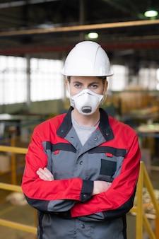 Портрет строителя в респираторе и каске, стоящего со скрещенными руками на строительной площадке