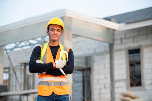 新しい家で働くヘルメット、建設現場での建設労働者の肖像画。