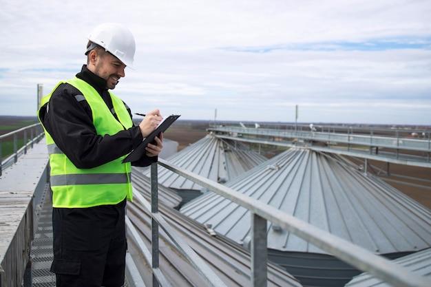 Портрет строителя, стоящего на крышах высоких резервуаров для хранения силосов и работающего на планшетном компьютере