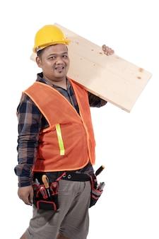 ヘルメットとユニフォームで木の板を運ぶコンストラクターの肖像画