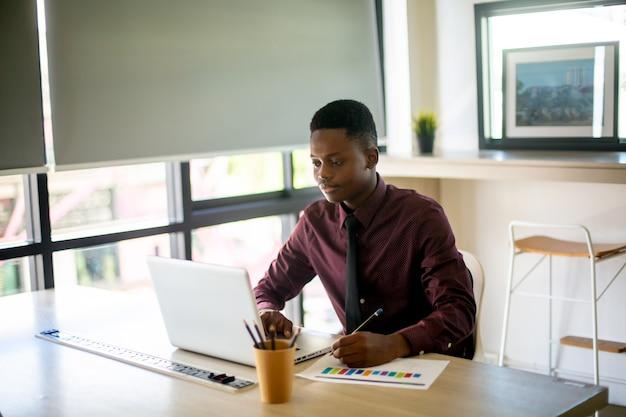 Портрет современного афро-американского мужчины, использующего ноутбук, сидя за столом в кафе, копией пространства