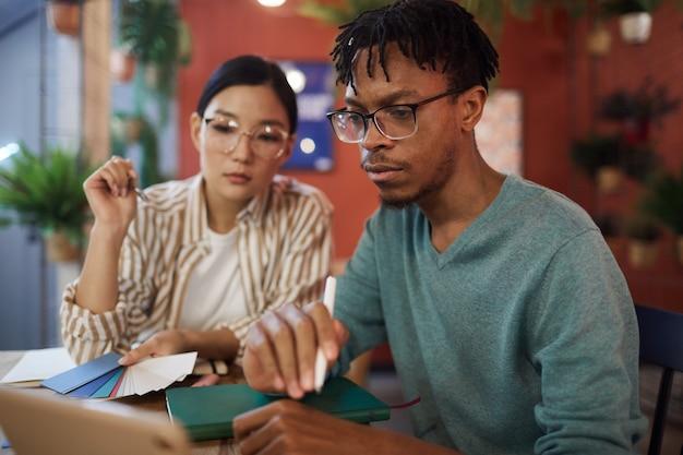 Портрет современного афроамериканца, использующего ноутбук во время учебы за столиком в кафе