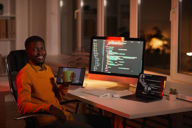 Портрет современного афро-американского мужчины, пишущего код и смотрящего в камеру, расслабляясь на рабочем месте с кофейной кружкой, копией пространства