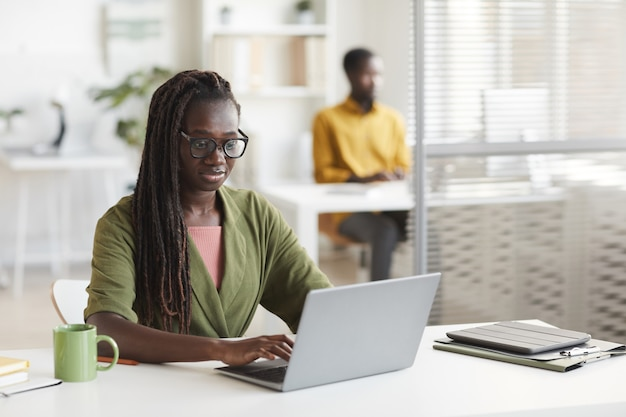 흰색 사무실 인테리어, 복사 공간에 책상에서 작업하는 동안 노트북을 사용하는 현대 아프리카 계 미국인 여자의 초상화