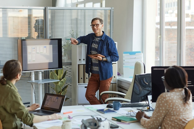 Портрет современного бизнесмена, указывающего на цифровой экран во время презентации на собрании команды в офисе разработки информационных технологий, копировальное пространство