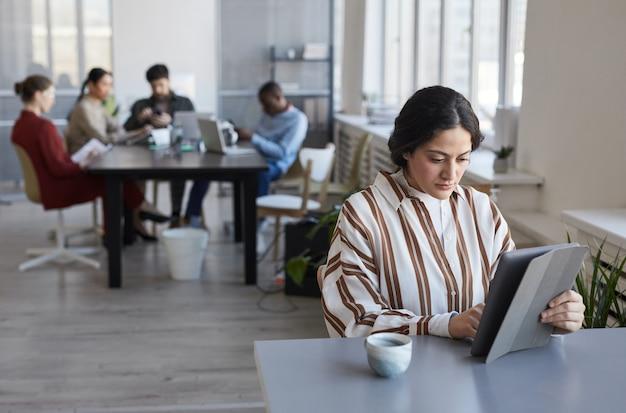 Портрет современной ближневосточной бизнес-леди, использующей цифровой планшет во время работы за столом в офисе с командой в фоновом режиме, копией пространства