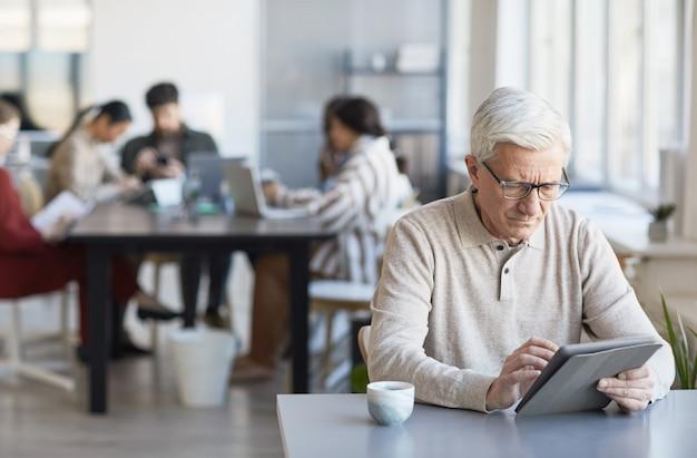 Портрет современного старшего мужчины, использующего цифровой планшет во время работы за столом в офисе с командой в фоновом режиме, копией пространства