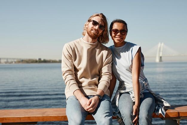 屋外の川でポーズをとっている間、カメラを見ている現代の若いカップルの肖像画、コピースペース